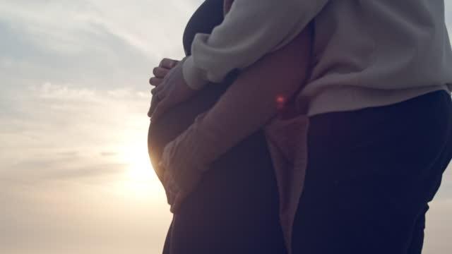 cu pregnant couple hugging on the beach at sunset - hålla handen bildbanksvideor och videomaterial från bakom kulisserna