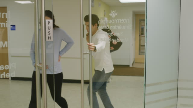 pregnant couple in labor rushing into hospital doorway / salt lake city, utah, united states - building entrance stock videos & royalty-free footage