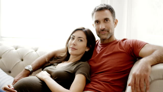 pregnant couple sitting on sofa in living room - 35 39 years stock videos & royalty-free footage