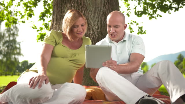 hd dolly: pregnant couple using tablet in the park - mid adult couple stock videos & royalty-free footage