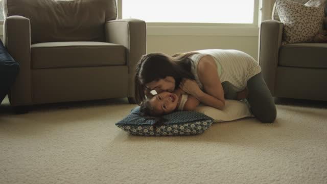 vidéos et rushes de femmes enceintes ethniques jouant avec son enfant dans le salon - soin prénatal