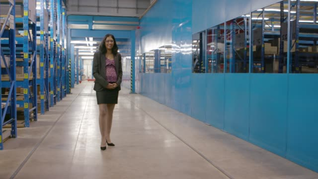 vídeos de stock e filmes b-roll de pregnant female manager standing in a warehouse - full length