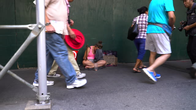 pregnant homeless woman hides her face in despair while begging for money on a busy sidewalk, 1 block from wall street / she holds a hand-written... - 物を乞う点の映像素材/bロール