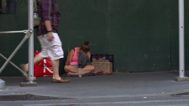 A pregnant homeless woman hides her face in despair while begging for money on a busy sidewalk 1 block from Wall Street / She holds a handwritten...