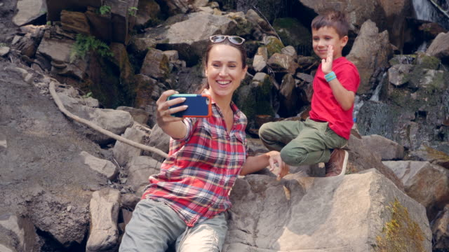 Pregnant mom with son taking selfie in front of waterfall