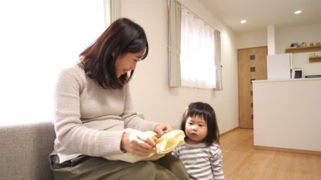 妊娠中の母親と彼女の娘は、彼女の期待の赤ちゃんのための贈り物を開きます - 贈り物点の映像素材/bロール