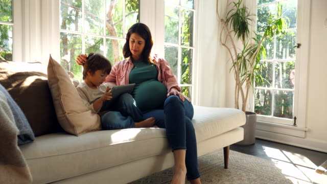 vidéos et rushes de ms pregnant mother and young son watching video on digital tablet while sitting on couch in living room - être à l'aise