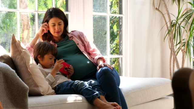 ms pan pregnant mother and young son watching video on smart phone while sitting on couch in living room - figli video stock e b–roll