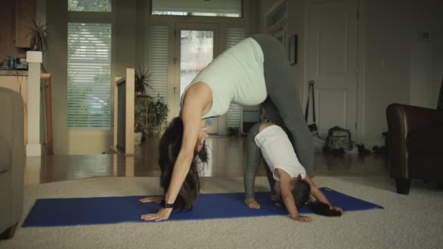 Zwangere moeder doen yoga in haar huis met haar peuter