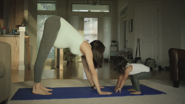 Pregnant mother doing yoga in her home with her toddler