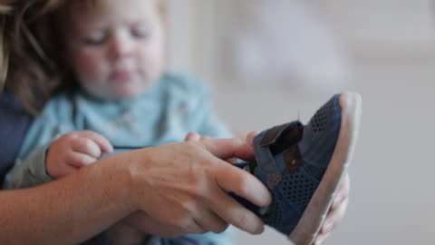pregnant mother dresses her young son - shoe stock videos & royalty-free footage