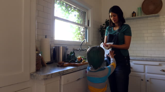 ms pregnant mother drying hands after washing vegetables with son in kitchen - drying stock videos & royalty-free footage