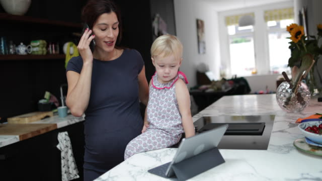 pregnant mother with child working from home - hot desking stock videos & royalty-free footage