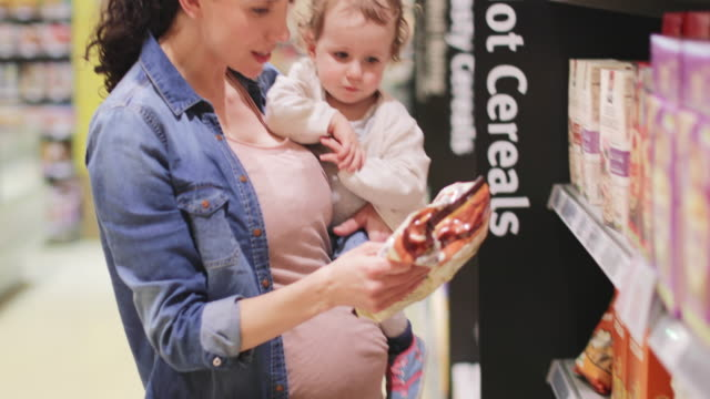 Pregnant mother with daughter grocery shopping