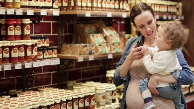 pregnant mother with daughter grocery shopping - preserve stock videos and b-roll footage