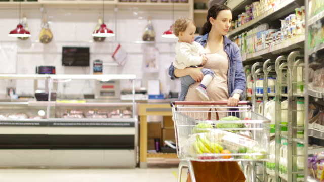 pregnant mother with daughter grocery shopping - milk bottle stock videos & royalty-free footage