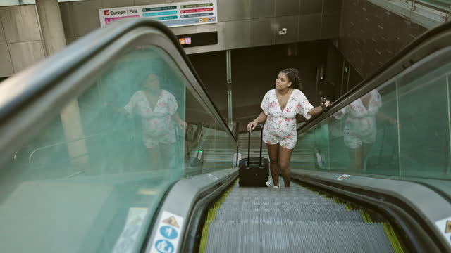 pregnant tourist moving up escalator with wheeled luggage - maternity wear stock videos & royalty-free footage