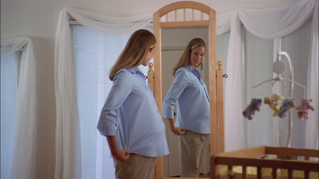 a pregnant woman admires her belly in the nursery mirror as her mother comes in to hug her. - mirror stock videos and b-roll footage