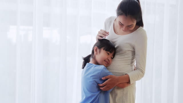 pregnant woman and a child hugging,medical system in china & hong kong.pregnancy/birth - apparato digerente umano video stock e b–roll