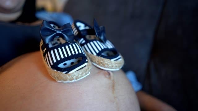 妊娠中の女性と赤ちゃんブーツ - 赤ちゃんの靴点の映像素材/bロール