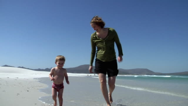 SLO MO MS DS Pregnant woman and boy (2-3) running on beach, Cape Town, South Africa
