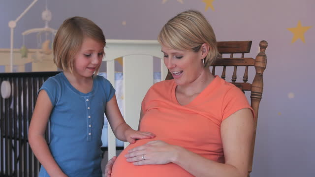 MS Pregnant woman and daughter (4-5) rubbing tummy in nursery room / Richmond, Virginia, USA.