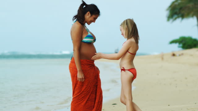 vídeos de stock, filmes e b-roll de pregnant woman and girl walking on beach - biquíni