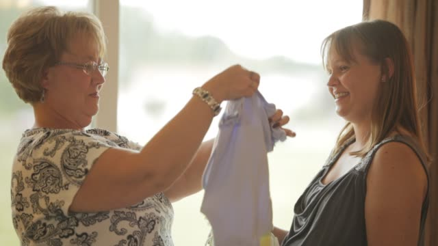 pregnant woman and her mother laughing and celebrating at her baby shower party - baby shower video stock e b–roll