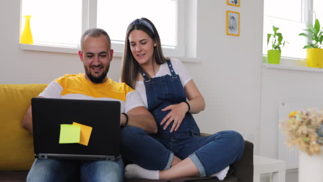 pregnant woman and man have video call on laptop at home - married stock videos & royalty-free footage