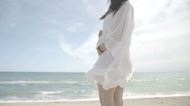 vidéos et rushes de m/s pregnant woman caressing her belly and looking at the horizon in a beach (summer), steadycam - blanc