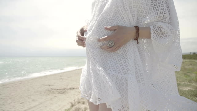vidéos et rushes de m/s pregnant woman caressing her belly and looking at the horizon in a beach (summer), steadycam - une seule femme d'âge mûr