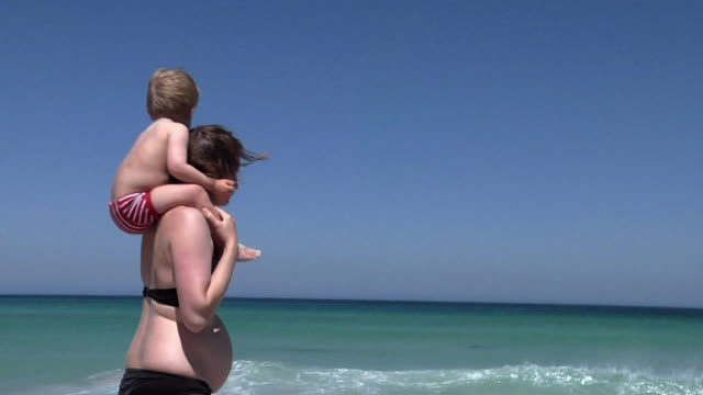 slo mo ms pan pregnant woman carrying boy (2-3) on shoulders on beach, cape town, south africa - swimwear stock videos & royalty-free footage