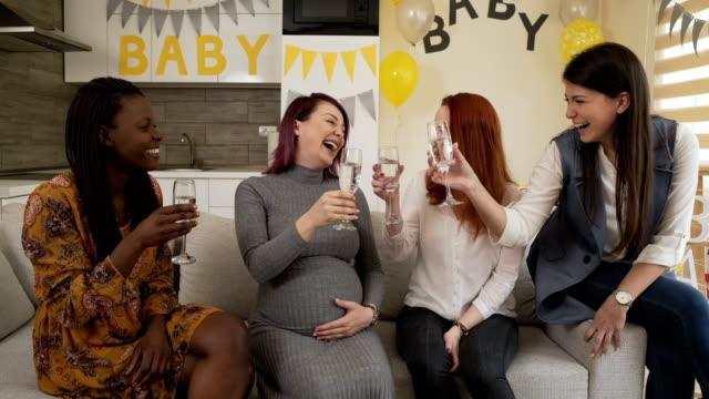 donna incinta che celebra la doccia del bambino con le amiche a casa. - baby shower video stock e b–roll