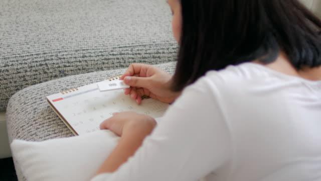 Schwangere Frau überprüfen Kalender mit Schwangerschaftstest