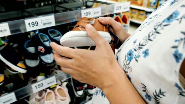 妊娠中の女性は、赤ちゃんやマタニティショップで赤ちゃんのブーツを選択します - 赤ちゃんの靴点の映像素材/bロール