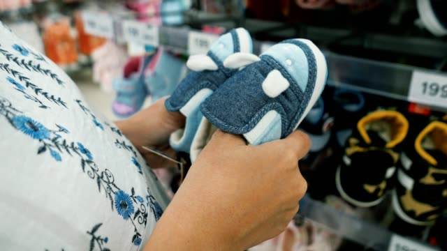 pregnant woman choosing baby booties in baby and maternity shop - small stock videos & royalty-free footage
