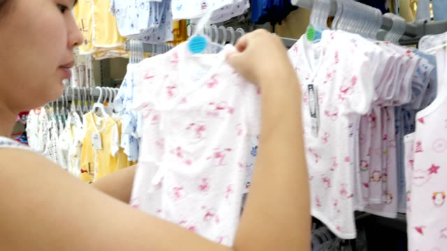 pregnant woman choosing baby clothing for her baby