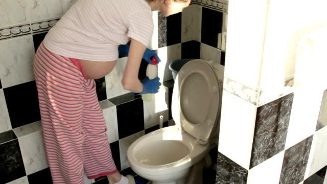 Schwangere Frau reinigt die Badezimmer