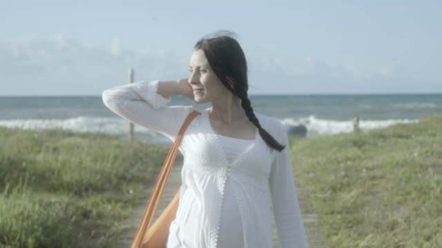 m/s pregnant woman coming back from doing yoga in the beach, steadycam - tunic stock videos & royalty-free footage