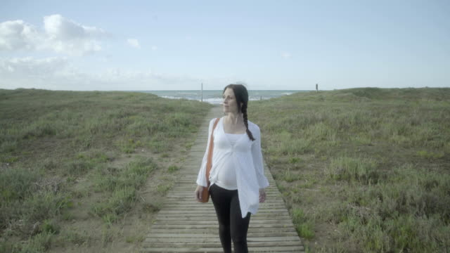 f/s pregnant woman coming back from doing yoga in the beach, steadycam - tunic stock videos & royalty-free footage