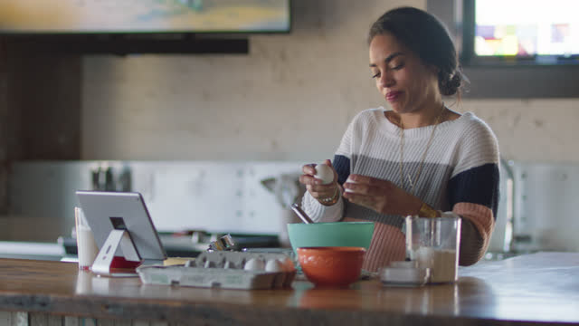 pregnant woman cracks a few eggs while video calling a friend - graphical user interface stock videos & royalty-free footage