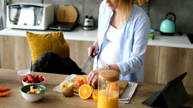 pregnant woman cutting fruit for healthy juice - television show stock videos and b-roll footage