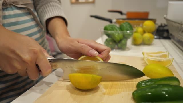 台所でレモンを切る妊娠中の女性 - 切る点の映像素材/bロール