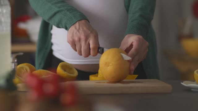 pregnant woman cutting up a grapefruit to juice it - vitamin a nutrient stock videos & royalty-free footage
