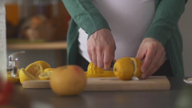 pregnant woman cutting up lemons and making a refreshing lemonade - juice extractor stock videos & royalty-free footage