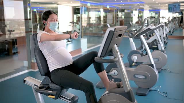 vídeos de stock, filmes e b-roll de gestante pedala dentro de casa enquanto se exercita na academia dentro de casa para se manter em forma e ativa durante a gravidez - smart