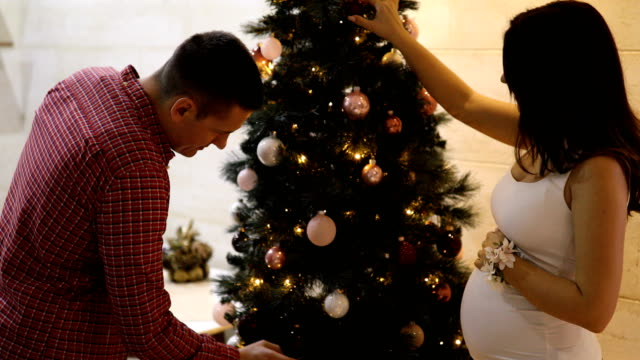 Pregnant woman decorating Christmas tree with her husband