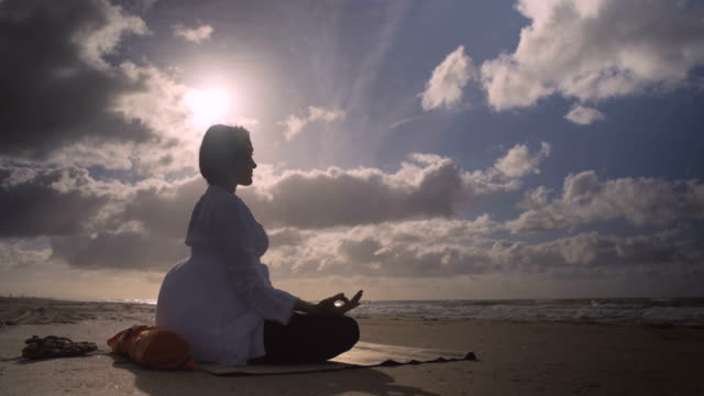f/s pregnant woman doing meditation in the beach - quarantenne video stock e b–roll