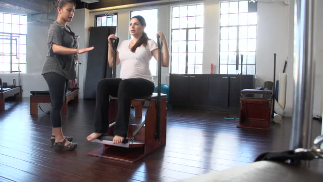 "vídeos y material grabado en eventos de stock de ""ms pregnant woman doing prenatal pilates on combo chair with instructor / beverly hills, california, united states"" - fisioterapia"