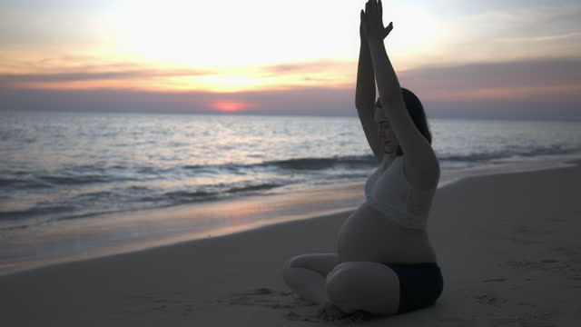 pregnant woman doing yoga exercise on sunset. the happy young expecting mother holding baby in pregnant belly. - prenatal care stock videos & royalty-free footage